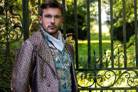 Portrait of handsome gentleman dressed in vintage costume standing in stately home courtyard with railings in background