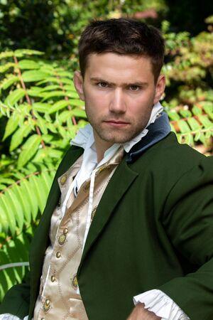Portrait of handsome yet grumpy gentleman dressed in vintage costume sitting on bench in garden