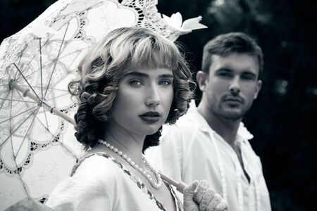 Handsome young couple in vintage clothing with beautiful lady looking at camera as handsome man looks at her, lovingly