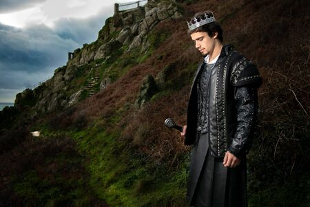 Handsome king with sword stands in contemplation with hill and parts of keep in the background