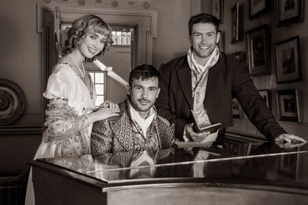 Vintage trio of people in period costume sitting around piano playing tunes and singing songs, laughing and smiling