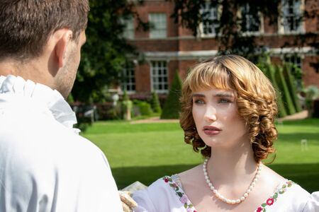 Beautiful young lady dressed in period costume confronting her husband or lover with stately home in background.