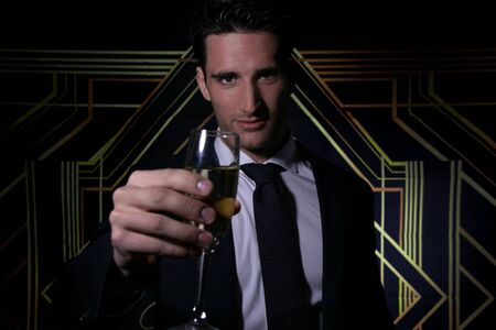 Handsome man in suit and tie in front of art deco backdrop holding a glass of sparkling wine to camera