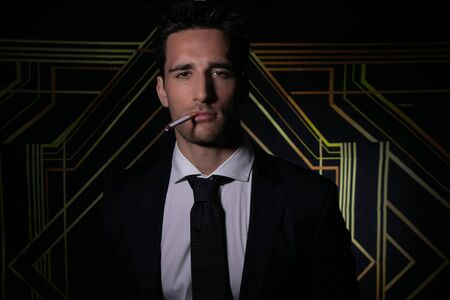 Portrait of handsome man in suit and tie in front of art deco backdrop with cigarette hanging from his lips Stock Photo