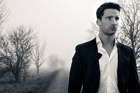 Handsome man wearing suit walking on a lonely foggy road Stock Photo
