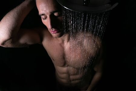 Sexy portrait of muscular man with sixpack abs under rainfall shower with eyes closed