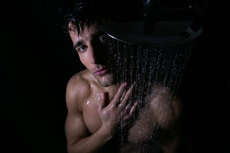Sexy portrait of handsome man with beard and brown eyes under a rainfall shower looking at camera
