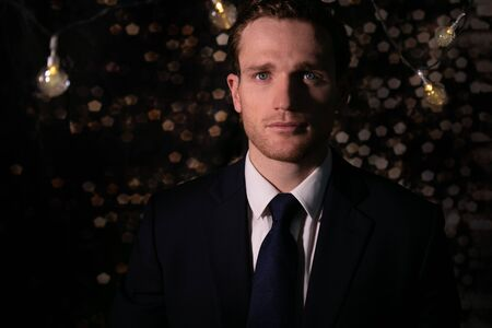 Good looking man in suit standing under string lights with bokeh blurred lights in the background and room for copy Imagens