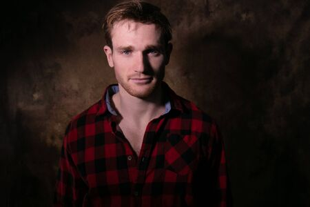 Portrait of good looking man with blue eyes and lumberjack shirt looking at camera with room for copy