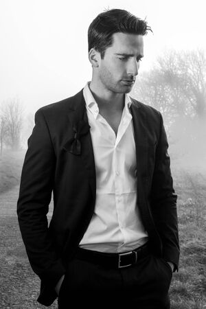 Handsome man wearing suit walking on a lonely foggy road Imagens