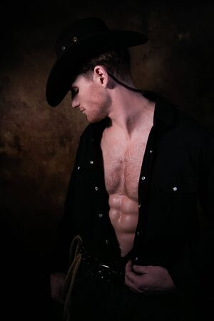 Profile of cowboy wearing hat with open black shirt revealing defined pecs and sixpack abs Stock Photo