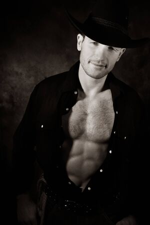 Portrait of handsome cowboy looking at camera with open black shirt revealing muscular pecs and sixpack abs Stock Photo