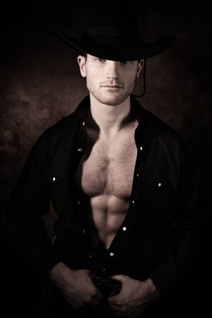 Portrait of handsome cowboy looking at camera wearing hat with open black shirt revealing defined pecs and sixpack abs Stock Photo