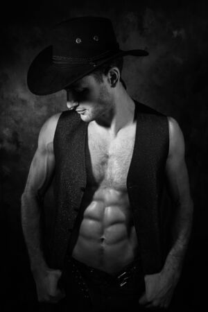 Profile of cowboy wearing hat and open waistcoat revealing musclar arms, defined pecs and sixpack abs