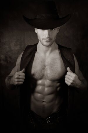 Handsome cowboy wearing hat with covered eye pulls open waistcoat to reveal defined pecs and muscular sixpack abs Stock Photo