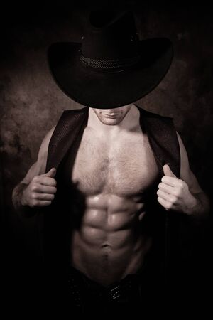 Attractive cowboy wearing hat covering his face opening waistcoat to reveal defined pecs and muscular sixpack abs Stock Photo
