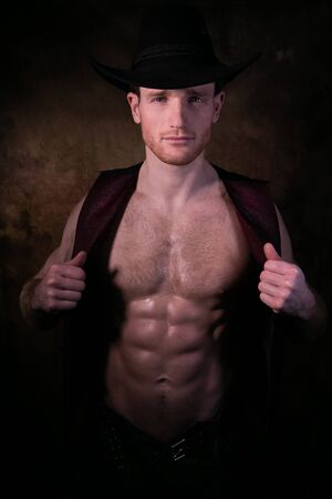 Handsome cowboy wearing hat, looking at camera, with waistcoat open to reveal defined pecs and muscular sixpack abs