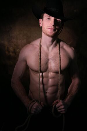 Handsome cowboy wearing a hat with barechest showing defined pecs and sixpack abs, muscular arms holding onto rope Stock Photo