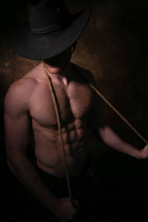 Shirtless cowboy wearing hat covering his face, holding rope around his neck with defined pecs and muscular sixpack abs Stock Photo
