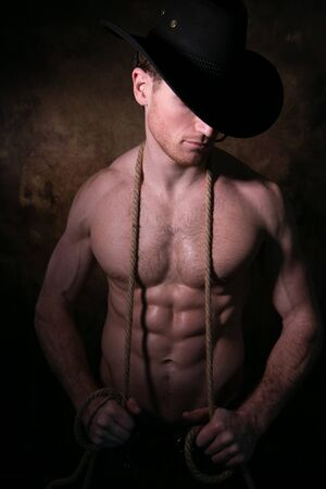 Shirtless cowboy wearing hat covering his face, holding rope around his neck with defined pecs and muscular sixpack abs Imagens