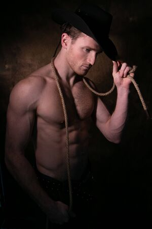 Handsome cowboy wearing a hat with barechest showing defined pecs and sixpack abs, muscular arms holding onto rope Imagens