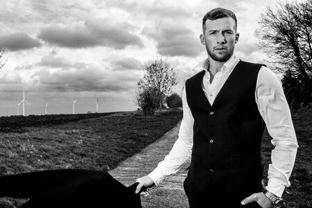 Handsome man in suit and waistcoat standing with fields and stormy sky behind him looking at camera.