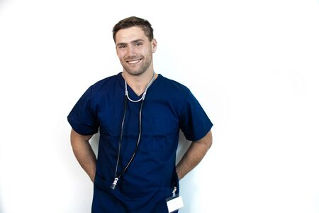 Smiling handsome male doctor in blue scrubs leaning against isolated white backdrop