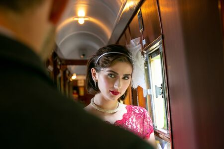 Portrait of beautiful woman in vintage dress standing in corridor of locomotive train with officer in uniform watching