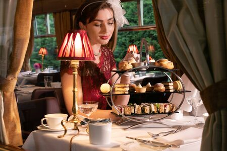Vintage, beautiful woman in red dress enjoying afternoon tea in train carriage with cakes, sandwiches and tea Stock Photo