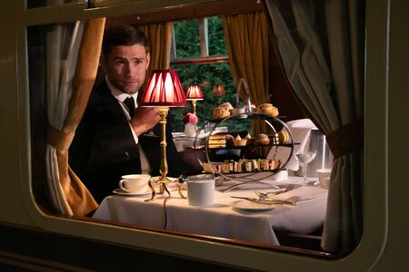 Vintage, handsome male in suit enjoying afternoon tea in train carriage with cakes, sandwiches and tea