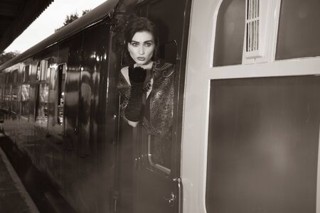 Attractive female wearing vintage evening dress leaning out of window of steam train and blowing a kiss Stock Photo