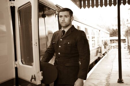 Handsome male British officer in vintage uniform at train station next to train