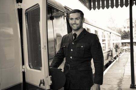 Handsome male British officer in vintage uniform at train station next to train, smiling Stock Photo