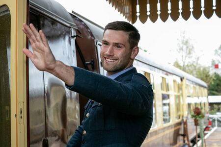 Handsome male British officer in vintage uniform at train station next to train waving and smiling