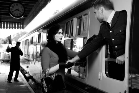 Vintage couple, man in uniform, woman in red dress, holding hands goodbye at train station as train departs