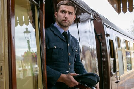Handsome male British officer in vintage uniform at train station, leaving train and holding his hat Stock Photo