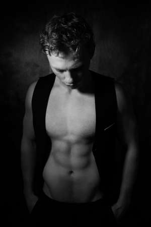 Handsome male with open waistcoat revealing defined pecs and muscular sixpack abs looking down