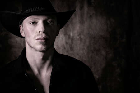 Portrait of handsome cowboy wearing black shirt with stetson hat looking at camera