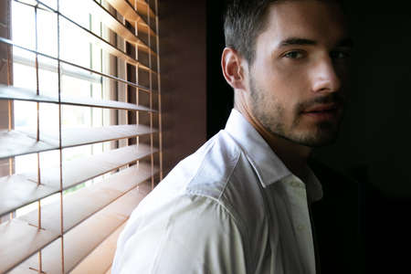 Portrait of handsome man with beard standing next to window with open shirt