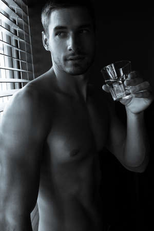 Portrait of handsome man with beard standing next to window with sixpack abs, pecs, drinking glass of water Archivio Fotografico