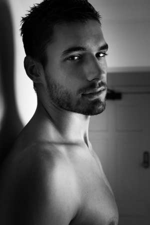 Portrait of handsome shirtless man looking at camera against white wall.