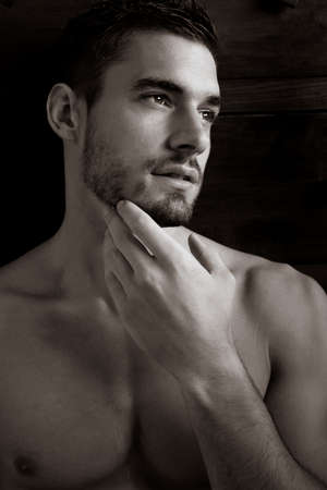 Portrait of enigmatic handsome man with beard looking away from camera