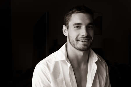 Portrait of handsome smiling young man with open shirt looking at camera