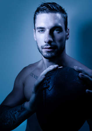 Portrait of young attractive topless muscular man with beard holding american football and looking at camera