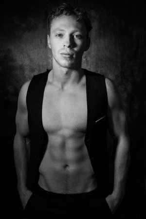 Handsome male with open waistcoat revealing defined pecs and muscular sixpack abs looking at camera