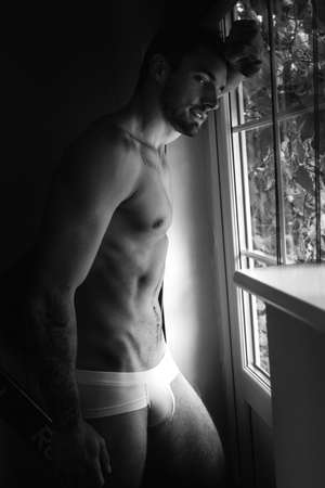 Portrait of handsome man with beard standing next to window with sixpack abs, pecs in his underwear Archivio Fotografico