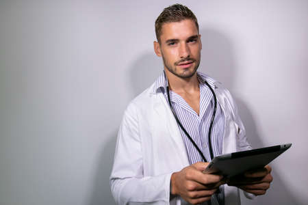 Good looking doctor wearing lab coat holding tablet and looking at camera on isolated background 版權商用圖片