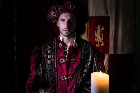 Portrait of handsome king with beard dressed in costume looking at camera with candle in foreground Archivio Fotografico