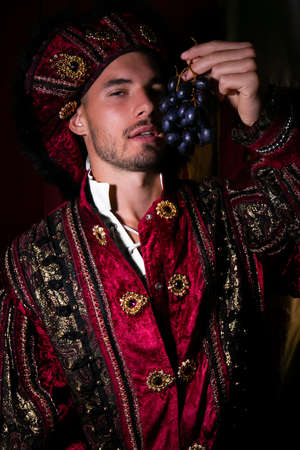 Portrait of handsome king with beard dressed in costume eating grapes and looking at camera