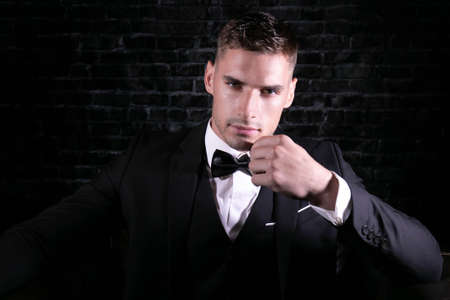 Portrait of handsome man wearing tuxedo with bowtie looking at camera